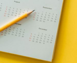 close up top view on white calendar with pencil and month schedule to make appointment meeting or manage timetable each day lay on yellow color background for planning work and life concept